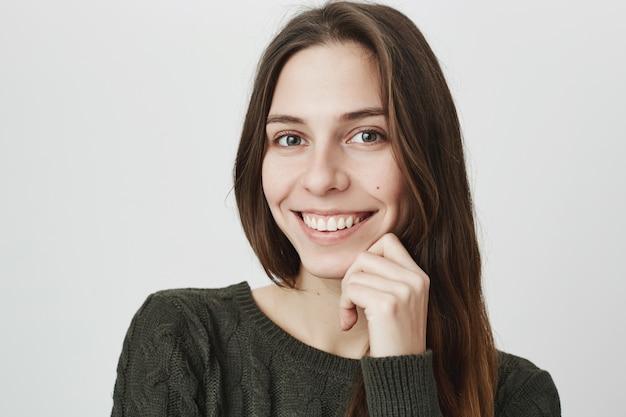 Женственная усмехаясь счастливая женщина смотря камеру