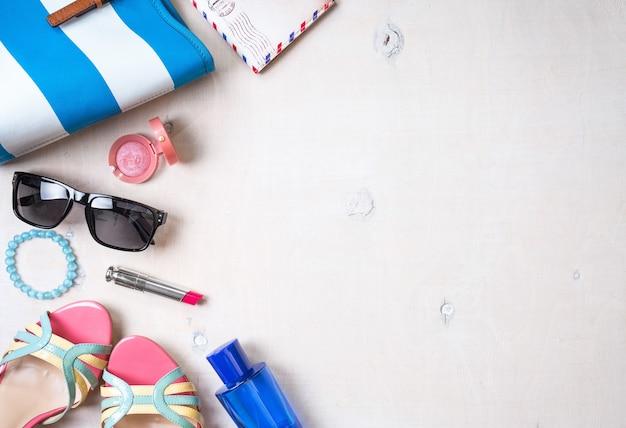 フェミニンな夏の背景。夏の女性のアクセサリーのセット:サングラス、靴、パスポート、青い縞模様のバッグ、ピンクの口紅、赤面、白い木の背景に香水。