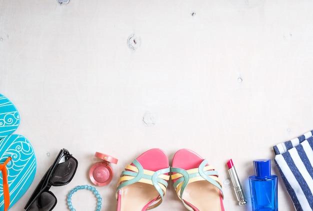 フェミニンな夏の背景。夏の女性のアクセサリーのセット:サングラス、靴、スリッパ、青い縞模様のバッグ、ピンクの口紅、赤面、白い木の背景に香水。