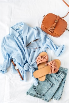 Женственная летняя пляжная модная композиция с блузкой, тапочками, сумочкой, солнцезащитными очками, часами, джинсовыми шортами на белом