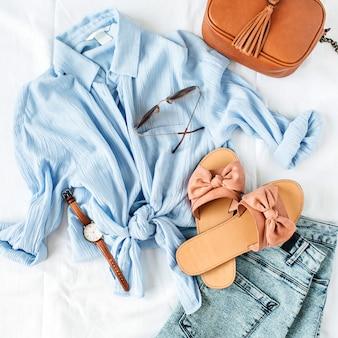 白い表面にブラウス、スリッパ、財布、サングラス、時計、ショーツを備えたフェミニンな夏のファッション構成