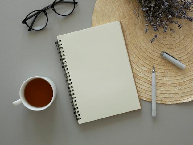 フェミニンなテーブルフラットレイアウトのモックアップ。ドライフラワー、開いたノートブック、コピースペースとお茶