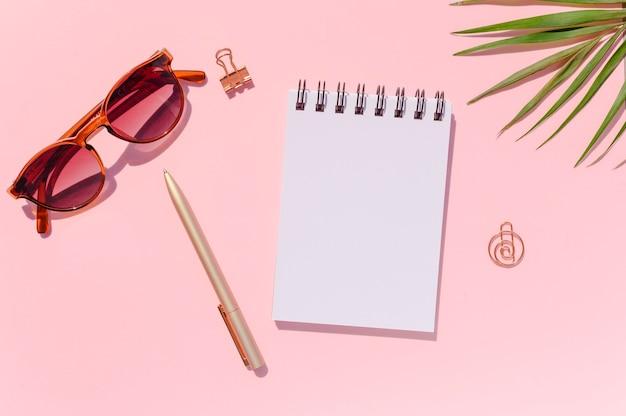 Женский макет заметок. тетрадь спирали взгляда сверху с ручкой, солнечными очками и пальмовым листом на розовой предпосылке. копировать пространство