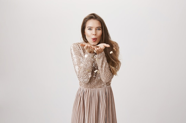 Женственная женщина дует золотое конфетти в вечернем платье