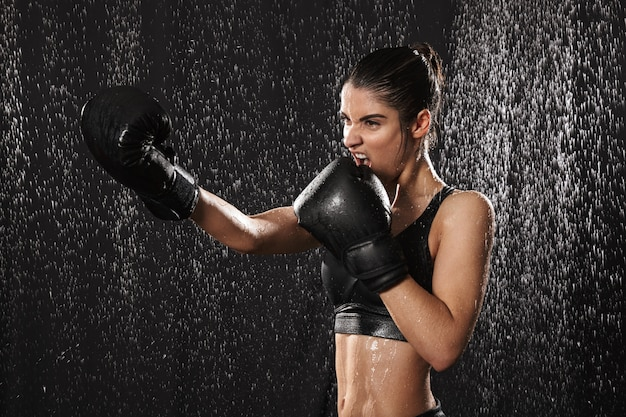 Feminine woman fighter 20s in sportswear and black boxing gloves throwing punches while training under rain drops, isolated over dark background
