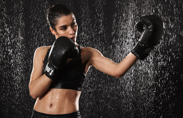 Feminine woman fighter 20s in sportswear doing sports exercises or practising in black boxing gloves while throwing punches under rain drops, isolated over dark background