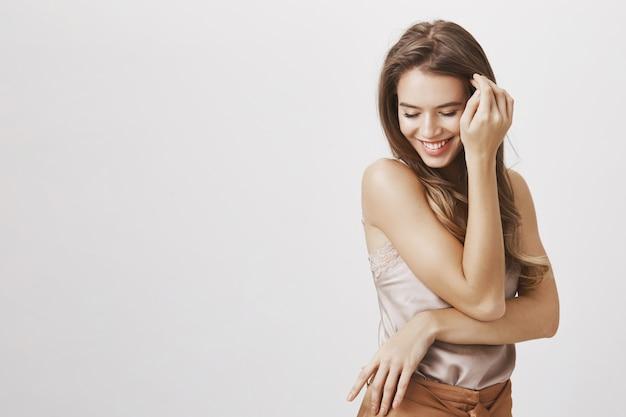 Женственная женщина смотрит вниз, улыбается и трогает волосы