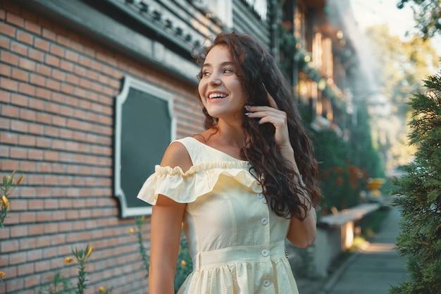 ポーズ若い笑顔の女性のフェミニンな女性の肖像画