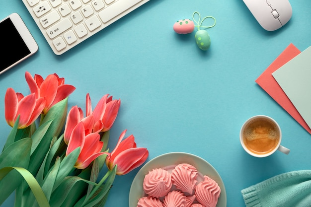 Feminine working space with cotton sweater, keyboard, mobile phone, plate of marshmallow and cup of coffee