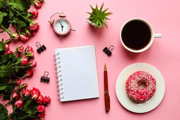 メモ帳ペン目覚まし時計花カップコーヒーとピンクのドーナツとフェミニンな職場