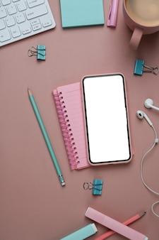 Женское рабочее место с умным телефоном, ноутбуком и канцелярскими принадлежностями на розовом фоне.
