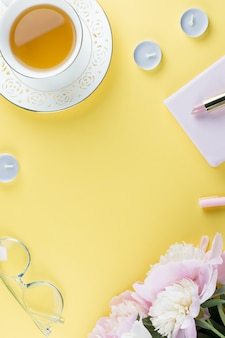Feminine workspace with diary, peony flowers, cosmetics, green tea