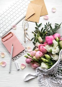 キーボード、バラの花、白い木製の背景に事務用品とフェミニンなワークスペース。オンライン作業のコンセプト