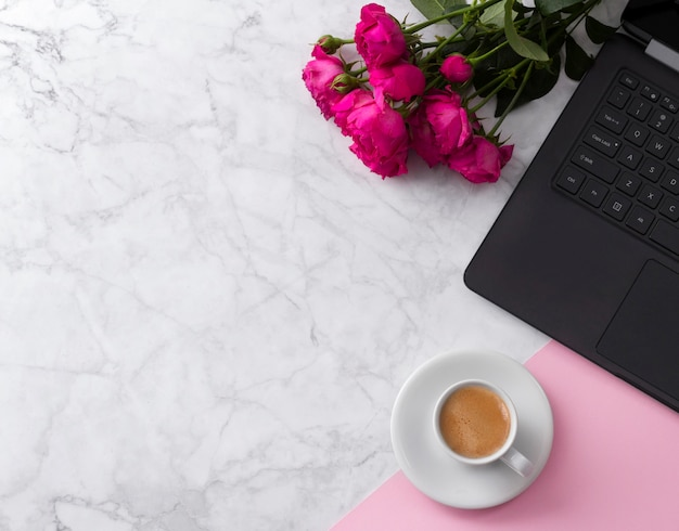 Feminine workspace with laptop computer, bouquet of roses and coffee on a marble table.