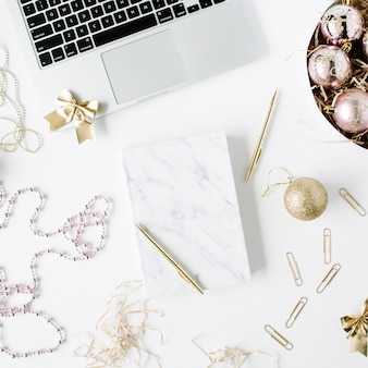 Feminine workspace with laptop, marble diary, golden pen, christmas decoration, christmas balls, tinsel, bow on white background.