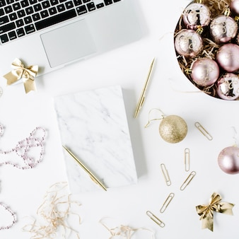 Feminine workspace with laptop, marble diary, golden pen, christmas decoration, christmas balls, tinsel, bow on white