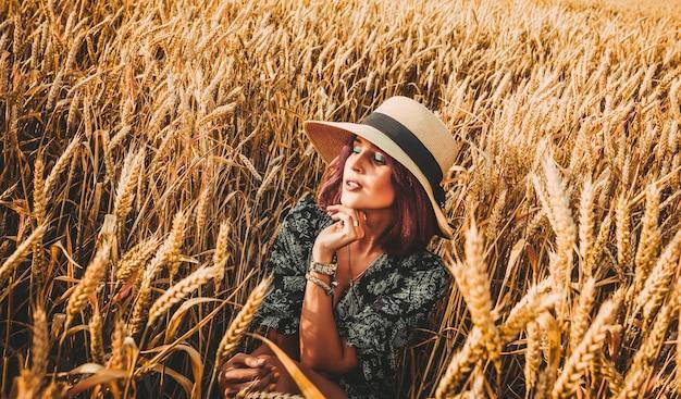 여성 스러움, 아름다움, 여행 개념입니다. 어떤 종류의 곡물의 키 큰 줄기 사이에서 떠오르는 태양의 밝은 빛, 아름다운 모자를 쓴 여자.