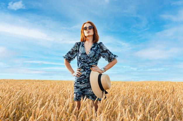 여성 스러움, 아름다움, 여행 개념입니다. 떠오르는 태양의 밝은 빛 속에서, 어떤 종류의 곡물의 키 큰 줄기 사이에서, 여자.