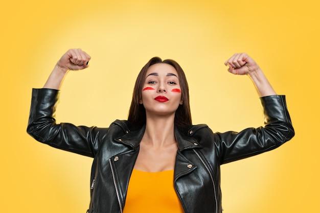 페미니즘, 걸파워, 그리고 여성의 평등권과 독립의 개념. 가죽 재킷을 입은 백인 젊은 여성이 팔뚝을 보여줍니다. 격리. 노란색 배경입니다. 복사.