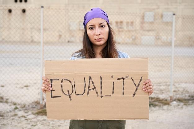 平等デモバナーを言っているプラカードを保持しているフェミニストの女性