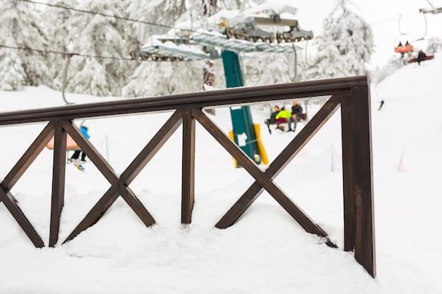 バックグラウンドでスキーリフトと柵とスキースロープ