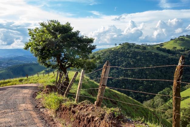 Забор и дерево на переднем плане с голубым небом и холмом на заднем плане. сельская местность бразилии