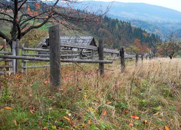 Fence of autumn mountain garden near farmstead