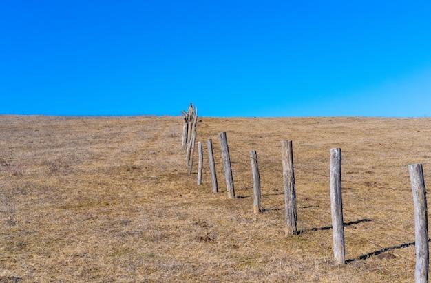 Забор в поле из деревянных сундуков.