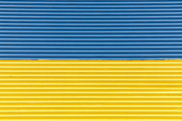 Fence painted in blue and yellow colors of ukrainian flag