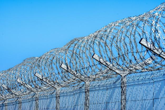Забор с колючей проволокой против голубого неба с облаками