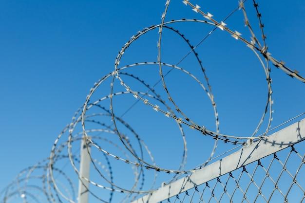 有刺鉄線、青空を背景にした有刺鉄線の柵。