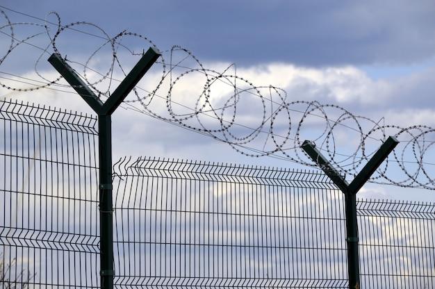 Забор с колючей проволокой на синем небе