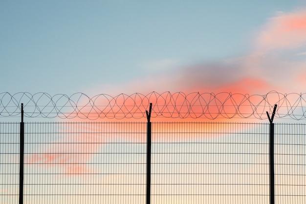 Забор с колючей проволокой. забор из проволочной сетки с красочным фоном неба.