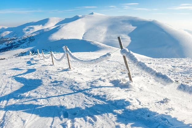 冬の高山の村で氷と雪の柵。山の風景