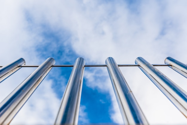 Fence with tall metal bars pointing to the blue sky with perspective viewed from below.