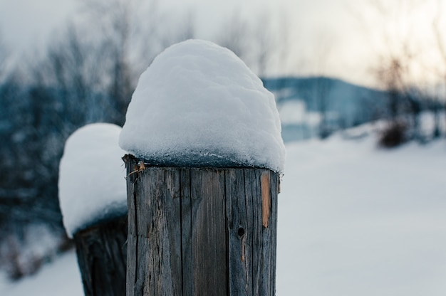 Fence wooden beam covered with snow cap. winter rural landscape, village or farm, snow-capped mountains and forest in the sunset