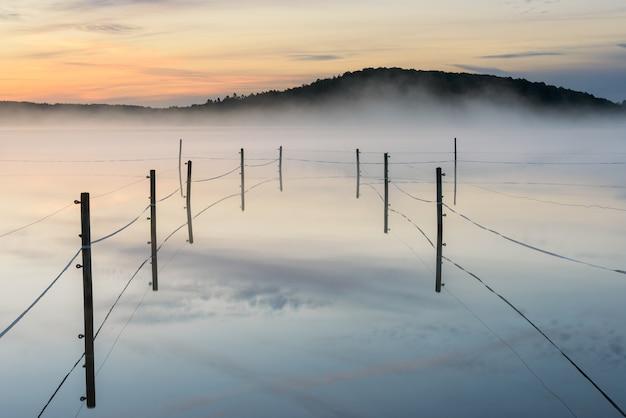 スウェーデン、ラダションの日没時の霧の湖のフェンスで囲まれたパドック