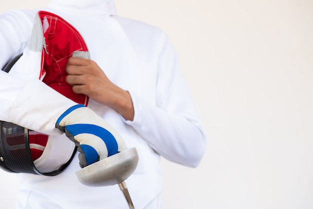 A fencer in white fencing suit and holding his mask and a sword on white background