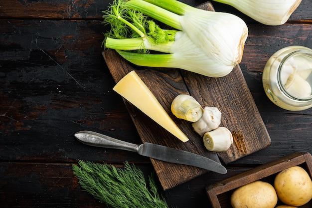 古い木製のテーブルの上に、パルメザンチーズの原材料を使ったフェンネルとアーティチョーク、フラットレイ
