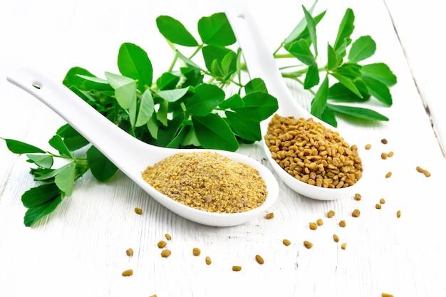 フェヌグリークの種子と挽いたスパイスを2つのスプーンで、木の板の背景に緑の葉のあるテーブルに