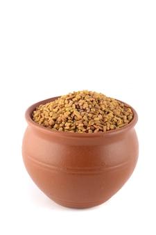 Семена пажитника в глиняном горшочке на белом фоне