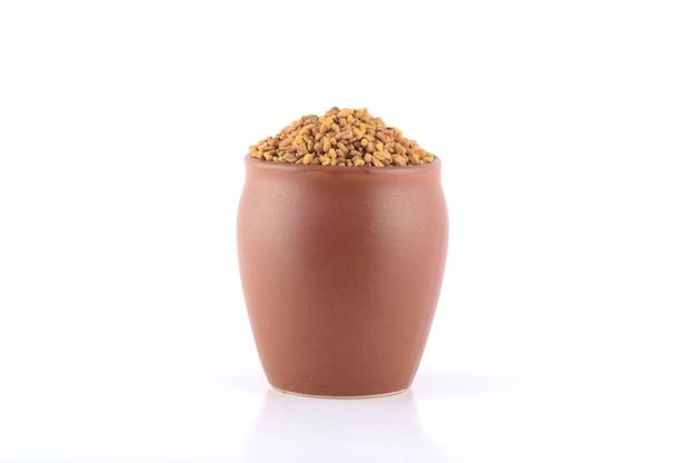 白い背景で分離された土鍋のフェヌグリーク種子