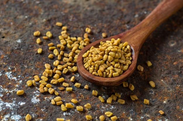 Семена пажитника в деревянной ложкой на текстурированном фоне