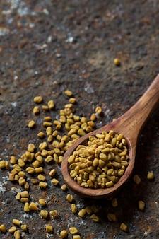 Семена пажитника в деревянной ложке на текстурированной поверхности