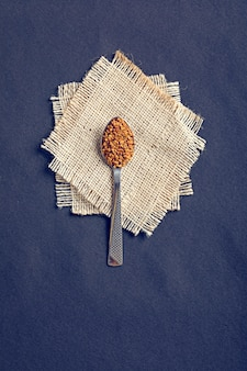 Fenugreek seeds in a spoon on black wooden board
