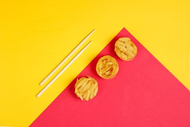 Ferawタリアテッレ麺と黄色い赤い紙の上の箸。ミニマルな食品のコンセプト。上面図