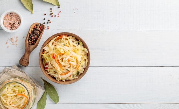 Ферментированная желтая капуста деревянная миска и банка с солью и перцем на белом столе