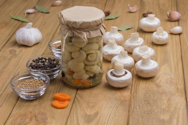 발효 제품. 통조림 버섯과 신선한 샴 피뇽 버섯이 담긴 유리 용기. 향신료 : 마늘, 양파, 베이 리프 테이블에. 건강한 겨울 음식, 가벼운 목재 표면. 공간 복사