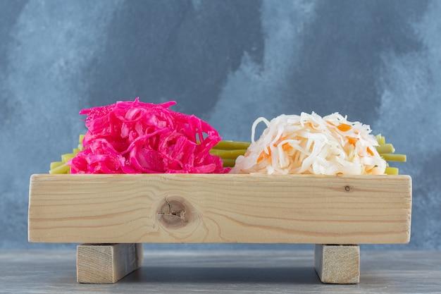 Квашеная капуста. разновидность квашеной капусты на деревянной доске.