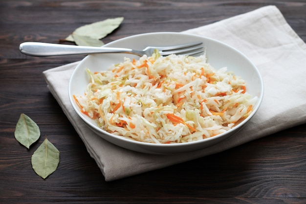 Fermented cabbage. vegan food. sauerkraut with carrot and spices in bowl on the dark background. trend food.